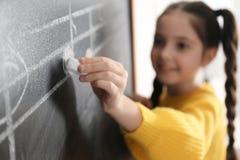 Petite fille écrivant des notes de musique sur le tableau noir dans la salle de classe photos stock