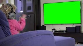 Petite fille émotive avec des écouteurs observant à l'écran vert de TV banque de vidéos