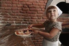 Petite fille étirant la pizza vers le haut de la pelle Photographie stock libre de droits