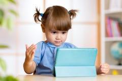 Petite fille étonnée regardant son PC de comprimé Photo stock