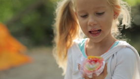 Petite fille étonnante avec des yeux bleus mangeant le gâteau banque de vidéos