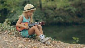 Petite fille étonnante avec le chapeau de paille se reposant par banque de vidéos