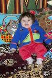 Petite fille étonnante s'asseyant dans le lit sur un lit avec les oreillers brodés photographie stock libre de droits