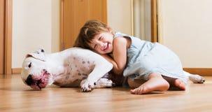 Petite fille étreignant le chien blanc Photos stock