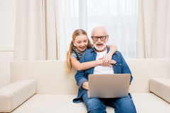 Petite fille étreignant le grand-père heureux à l'aide de l'ordinateur portable à la maison Photos libres de droits