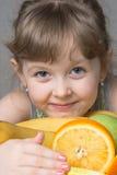 petite fille étreignant les fruits préférés Photo stock