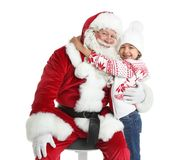 Petite fille étreignant Santa Claus authentique sur le fond blanc photographie stock