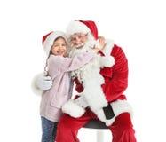 Petite fille étreignant Santa Claus authentique sur le fond blanc photo stock