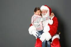 Petite fille étreignant Santa Claus authentique sur le fond gris photos stock