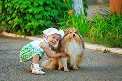 Petite fille étreignant un chien Photos libres de droits