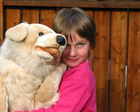 Petite fille étreignant un grand crabot de jouet de peluche image libre de droits