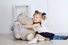 Petite fille étreignant un hippopotame de nounours dans le studio Photos stock