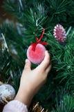 Petite fille accrochant le flocon de neige décoratif sur l'arbre de Noël Photos libres de droits