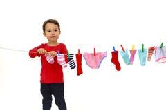 Petite fille accrochant ses vêtements pour sécher d'isolement photos libres de droits