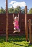 Petite fille accrochant sur la barre horizontale photographie stock libre de droits