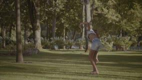 Petite fille active faisant la roue sur l'herbe verte banque de vidéos