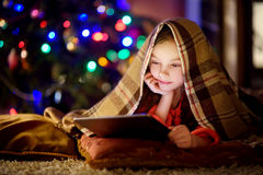 Petite fille adorable à l'aide d'un PC de comprimé par une cheminée la soirée de Noël photographie stock