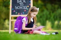 Petite fille adorable à l'aide du comprimé d'ordinateur tout en se reposant sur une herbe le jour d'été Photographie stock libre de droits