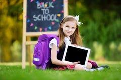 Petite fille adorable à l'aide du comprimé d'ordinateur tout en se reposant sur une herbe le jour d'été Images libres de droits
