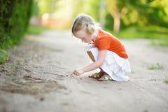 Petite fille adorable attrapant de petits babyfrogs Image libre de droits