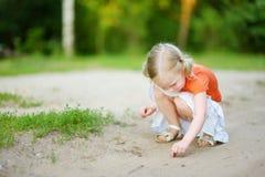 Petite fille adorable attrapant de petits babyfrogs Photographie stock libre de droits