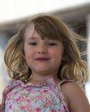 Petite fille adorable au visage rond avec les cheveux blonds sales très vent-soufflés photo stock