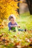 Petite fille adorable avec des feuilles d'automne Photos stock