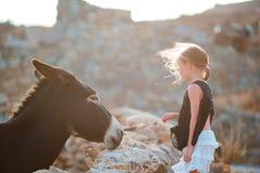 Petite fille adorable avec l'âne sauvage sur l'île grecque dehors Images stock