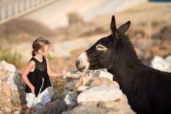 Petite fille adorable avec l'âne sur Mykonos Photo stock