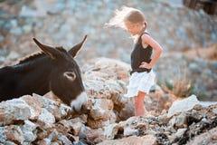 Petite fille adorable avec l'âne sur Mykonos Image libre de droits