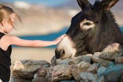 Petite fille adorable avec l'âne sur Mykonos Photo libre de droits