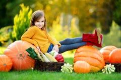 Petite fille adorable ayant l'amusement ensemble sur une correction de potiron Photos stock