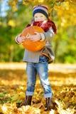 Petite fille adorable ayant l'amusement sur une correction de potiron le beau jour d'automne Photo stock