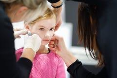 Petite fille adorable ayant le processus piercing d'oreille au centre de beauté Photographie stock libre de droits