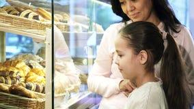 Petite fille adorable choisissant la pâtisserie dans l'étalage tout en faisant des emplettes avec sa mère clips vidéos