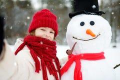 Petite fille adorable construisant un bonhomme de neige dans le beau parc d'hiver Enfant mignon jouant dans une neige Images stock