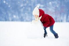 Petite fille adorable construisant un bonhomme de neige dans le beau parc d'hiver Enfant mignon jouant dans une neige Photos stock