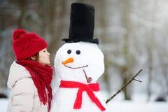 Petite fille adorable construisant un bonhomme de neige dans le beau parc d'hiver Enfant mignon jouant dans une neige Photo stock