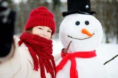 Petite fille adorable construisant un bonhomme de neige dans le beau parc d'hiver Enfant mignon jouant dans une neige Images libres de droits