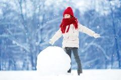 Petite fille adorable construisant un bonhomme de neige dans le beau parc d'hiver Enfant mignon jouant dans une neige Image stock