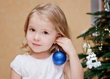 Petite fille adorable décorant un arbre de Noël Image libre de droits