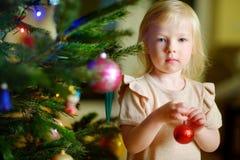 Petite fille adorable décorant un arbre de Noël Photos stock