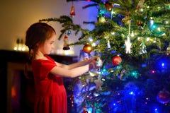 Petite fille adorable décorant un arbre de Noël Image stock