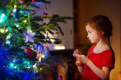 Petite fille adorable décorant un arbre de Noël Photo stock