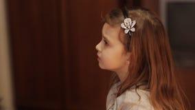 Petite fille adorable décorant un arbre de Noël avec les babioles en verre colorées à la maison banque de vidéos