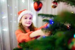 Petite fille adorable décorant un arbre de Noël avec les babioles en verre colorées Photo libre de droits