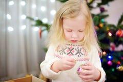 Petite fille adorable décorant un arbre de Noël avec les babioles en verre colorées Photos stock