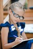 Petite fille adorable d'école avec des notes et des crayons extérieurs De nouveau à l'école Photographie stock libre de droits