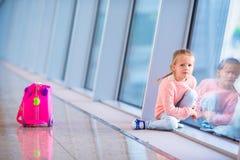 Petite fille adorable dans l'aéroport avec son embarquement de attente de bagage Images libres de droits