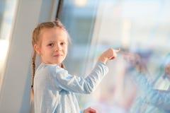 Petite fille adorable dans l'aéroport près de l'embarquement de attente de grande fenêtre Photo stock